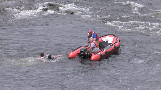 Rescue workers pull teens from river using boat